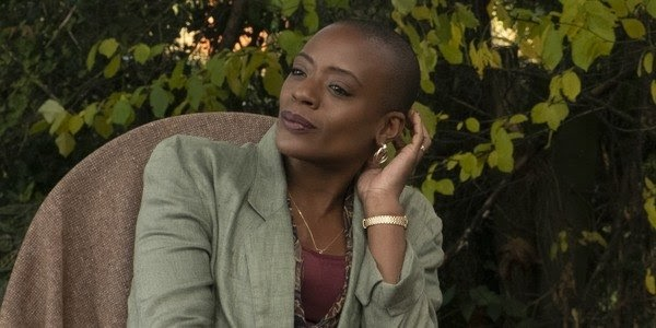 A still from 'The Haunting of Bly Manor'. Hannah Grose (T'Nia Miller) is shown in a mid shot, slightly off centre frame, sat in a chair against a leafy backdrop, presumably a bush. She is a Black woman, shaved head and incredibly youthful face and strong bone structure. She is wearing a sage green blazer with a burgundy top underneath. She has a gold watch on and is raising her right arm to touch her ear, from which dangles a large gold earring.