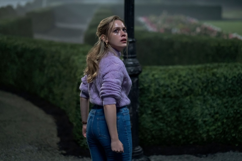 A still from 'The Haunting of Bly Manor'. Dani (Victoria Pedretti) is stood outside at night, in what looks like a maze, or some incredibly ornate gardens and bushes. She is centre frame,and shot from her head to her knees. She is turning back towards the camera and looking up, the moonlit is shining off the sweat on her forehead. She is in an 80s style outfit, with blue jeans and a purple polo neck jumper. She has long blonde hair, pale skin and a youthful complexion
