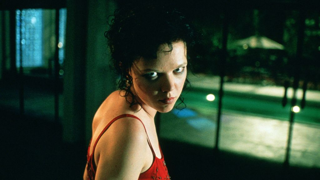 A still from 'The Rage: Carrie 2'. Rachel (Emily Bergl) is shown centre frame in close-up, her body is turned so she is looking over her shoulder, staring right down the camera with anger. She is wearing a red strappy dress and her black hair is curled and piled on top of her head. Behind her are doors that lead out onto a patio and pool area.