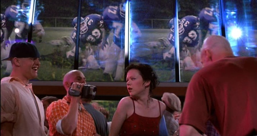 A still from 'The Rage: Carrie 2'. Rachel (Emily Bergl) is shown in the centre of the image, being harassed by jocks, one of whom is holding a camcorder. They are all in 90s/early 00s clothing and Rachel is in a red strappy dress, its clearly a party event. Above their heads you can