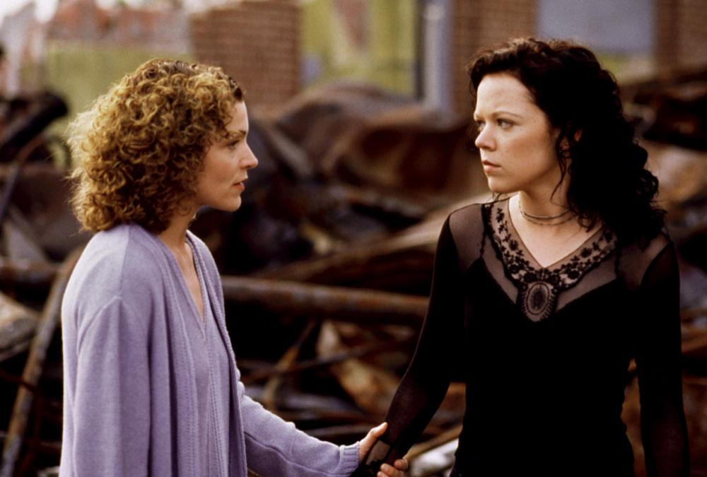 A still from 'The Rage: Carrie 2'. Sue Snell (Amy Irving), the school guidance counsellor stands next to a burnt out rubbish pile with Rachel (Emily Bergl). Sue is holding Rachel's wrist as if preventing her from leaving. Sue wears a matching lilac top and cardigan, she is in her 40s/50s and has tight curled dark blonde hair. Rachel is dressed in a gothic style, all black top with mesh and lace accents and her hair is also dark and curled similarly to Sue's.
