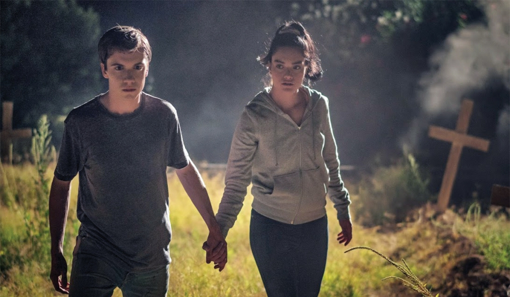 A still from 'The Unhealer'. Kelly (Elijah Nelson) walks through an overgrown makeshift graveyard holding the hand of Dominique (Kayla Carlson). They are both teenagers wearing simple clothes, t-shirts, hoodies and jeans. The image is set at night.