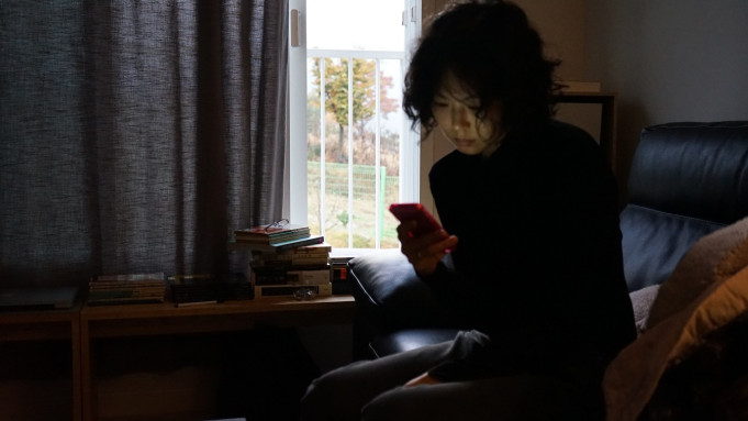 A still from 'The Woman Who Ran'. Gamhee (Kim Minhee) sits to the right of the image in a darkened living room with the curtains pulled nearly completely across. She is a South Korean woman with wavy, short dark hair. Her face is lit up by her phone screen as she aimlessly scrolls on the pink device. She sits on a sofa wearing a black jumper, the table next to her has a scattering of books over it.