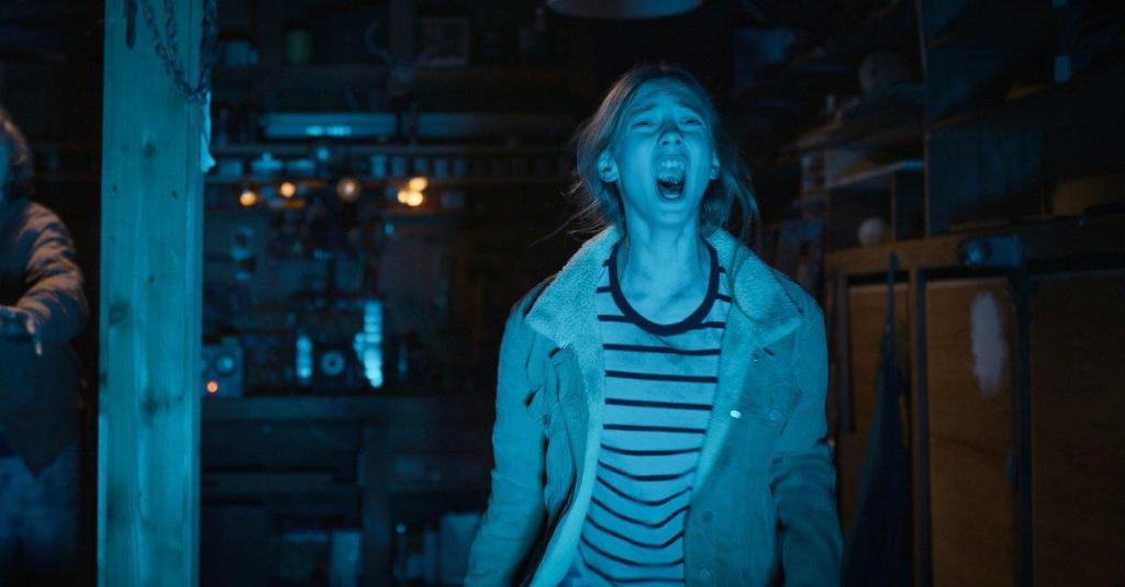A still from 'They Reach'. Jessica (Mary Madaline Roe) is shown in mid shot screaming at an unknown presence. The image is lit with white blue light. She is standing in a basement and there is lots of small machines and DIY objects behind her. Jessica's long, blonde hair is pulled back into a ponytail and she wears a black and white striped t-shirt with a denim jacket with sheepskin collar.