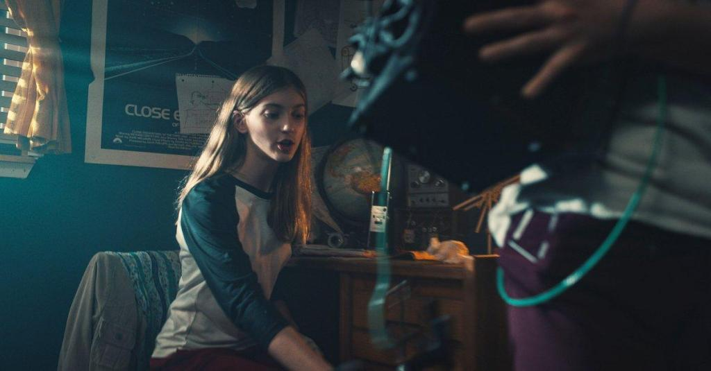 A still from 'They Reach'. Jessica (Mary Madaline Roe) sits in her bedroom at her desk. There is radios and robots all over the desk as well as a globe. Her room is blue and behind her is a poster for 'Close Encounters of the Third Kind'. In the foreground of the image is the lower half of another person, holding a machine. Jessica wears a blue and white baseball top and red pants, her hair is long and blonde.