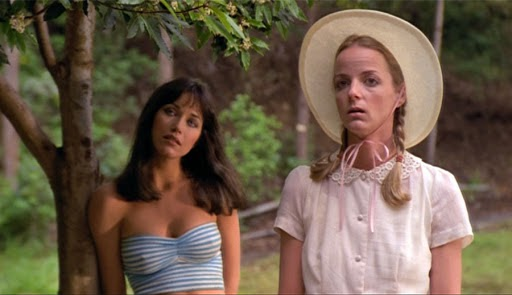 A still from 'Tourist Trap'. Eileen (Robin Sherwood) and Molly (Jocelyn Jones) are shown in mid shot amongst some trees. Eileen is a brunette, very attractive, wearing a boob-tube top that highlights her slender frame whereas Molly is shown to be quite modest in a white shirt with lace peter pan collar and a bonnet, her blonde hair worn in pigtails.