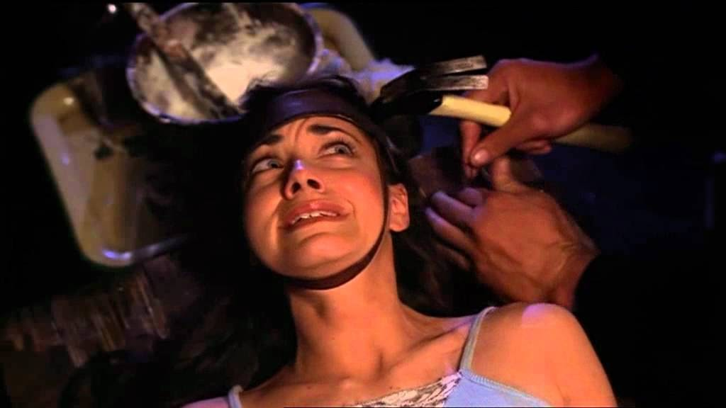A still from 'Tourist Trap'. A woman is shown in close-up strapped to a wooden bed with a leather strap around her jaw and skull, she looks terrified. A man's hands can be seen to the right of the shot, holding a hammer.