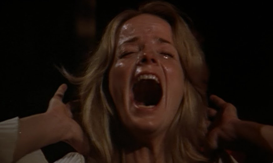 A still from 'Tourist Trap'. Molly (Jocelyn Jones) is shown in close-up screaming and crying, her face is wet with sweat and tears, her head is thrown back and her hands are behind her head.