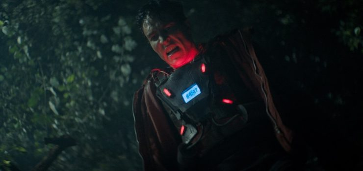 A still from 'Tirggered'. A 20-something man stands in the middle of a darkened wood, shown in midshot. He is wearing a bomb vest and his face is lit up in red by the lights on the vest. He looks sweaty and his mouth is open in anguish.
