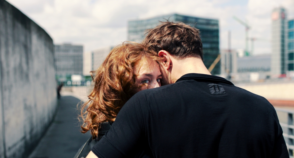 Still from Undine. Paula Beer faces the camera, her head tucked into the shoulder of a man, locked in an embrace. She looks right at the lens. In the background are glass buildings and cranes.