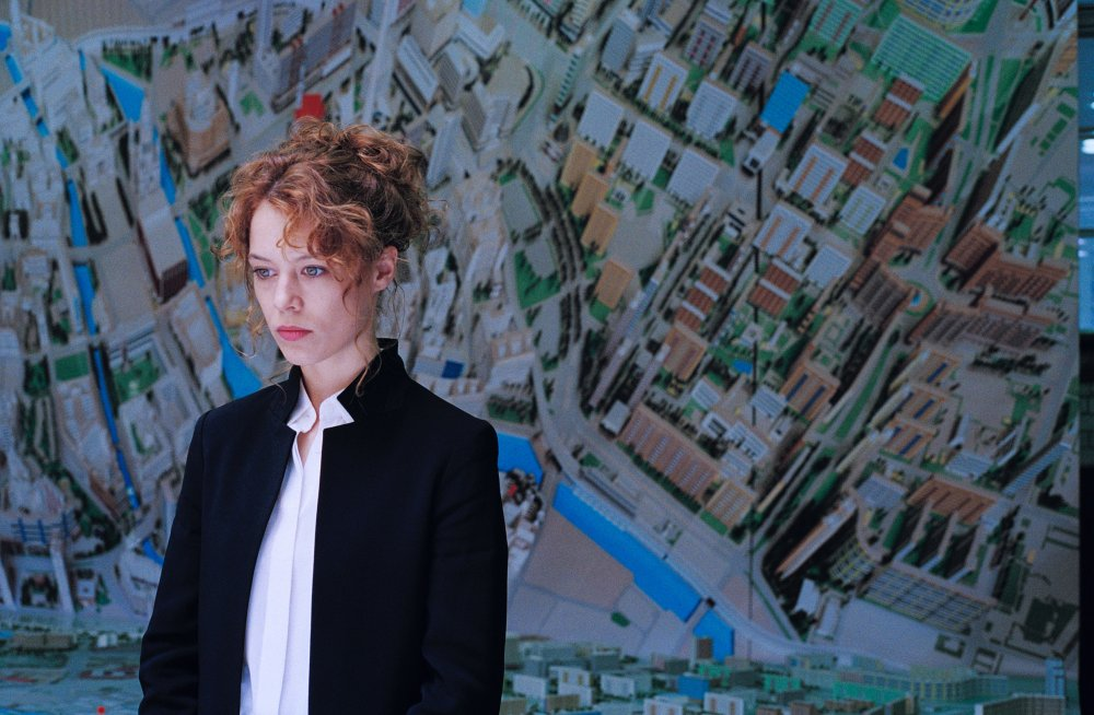 A still from 'Undine'. City historian Undine (Paula Beer) stands in front of an aerial cityscape illustration spanning the wall. She is to the left of the image, shown in mid shot, wear a white blouse and black blazer. She is of fair skin, in her 30s with red, curly hair piled on her head.