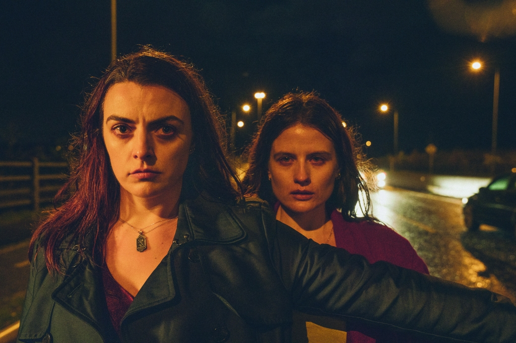 Still from 'Wildfire'. Nora-Jane Noone is in the foreground, her arm outstetched protectively, Nika McGuigan standing behind her. They are on a main road at night, the tarmac wet and the lights cast an orange glow over everything.