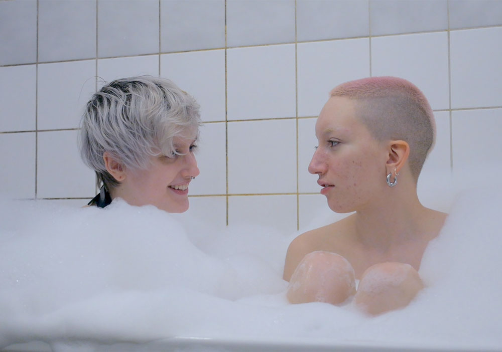 A still from documentary 'Always Amber'. Amber is shown sat in a bath with their friend, bubbles are almost up the the pair's necks. The image is very white and peaceful.