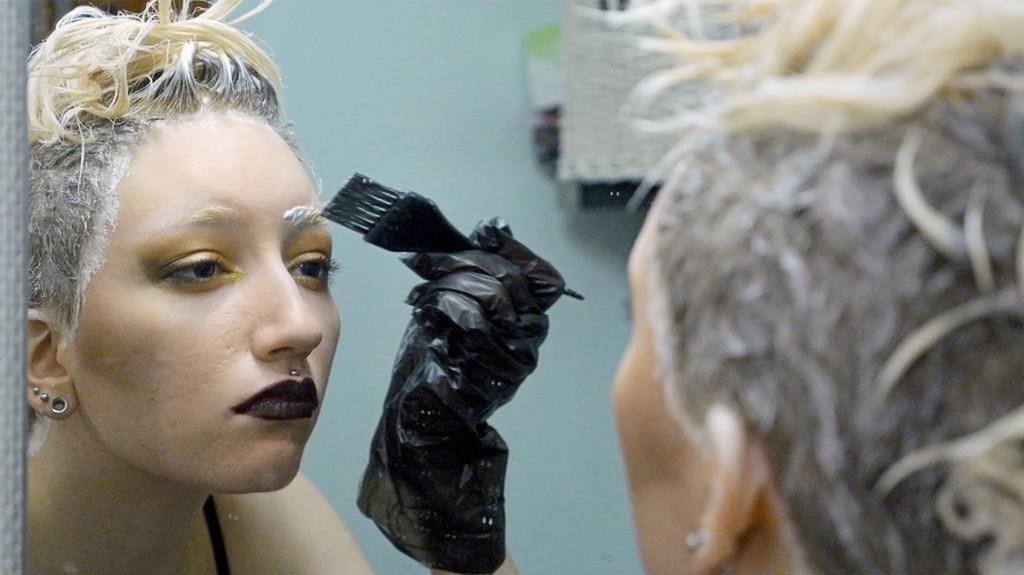 A still from documentary 'Always Amber'. Amber is shown in close-up in the bathroom mirror. They have a head covered in bleach and are in the process of brushing bleach on their eyebrows. They have elaborate gold and brown eyeshadow on and black lipstick, with a piercing in their cupid's bow.