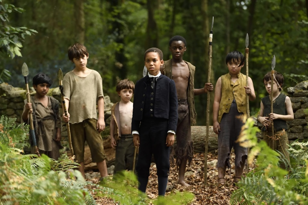 A still from 'Come Away'. Peter (Jordan Nash) is shown centre frame in a wide shot, flanked by 'Lost Boys' — 3 on either side of him. Peter is a boy of about 10 years old, wearing a black 18th century suit and white shirt. He is dark skinned with short black hair.  The boys behind him range in ages from 6 to around 13 and of varying ethnicities and heights. The 'lost boys' are all wearing scruggy clothing in neutral tones, all tattered and worn, all holding makeshift spears. Peter stands out in contrast to them in the forest setting they are stood in.