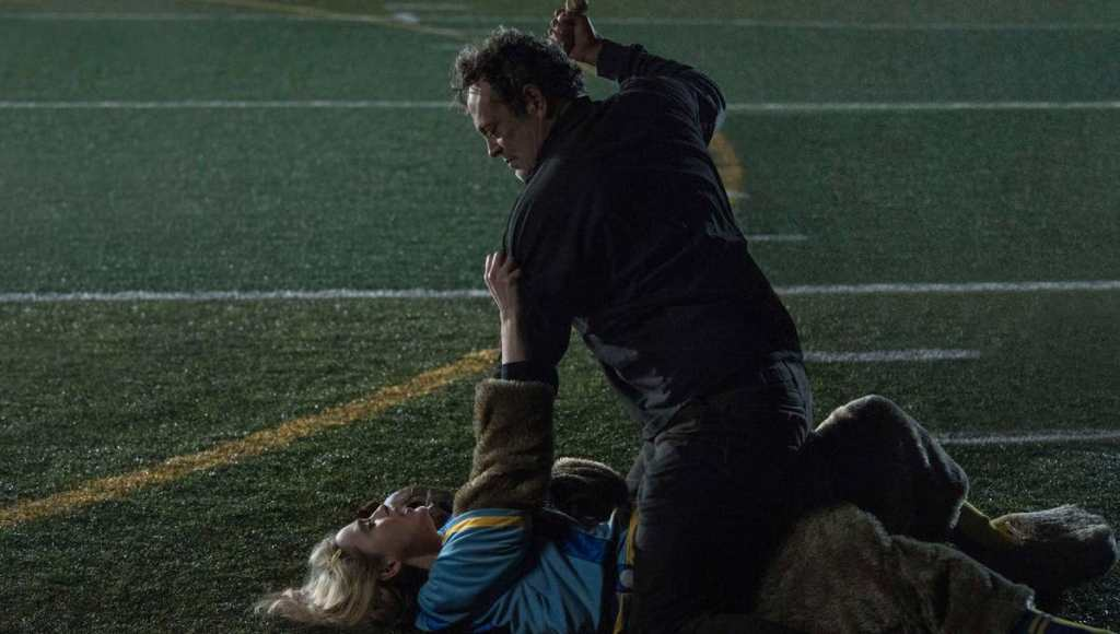 A still from 'Freaky'. Millie Kessler (Kathryn Newton) is shown struggling on the floor of a American Football pitch as she is attacked by the Blissfield Butcher (Vince Vaughn), who weirds a knife in his hand. Millie is on the ground, her blonde hair splayed across the grass, wearing a mascot uniform of some kind of furry creature. The Blissfield Butcher is on top of her, straddling her, wearing all black. He is a man in his 40s with dark hair.