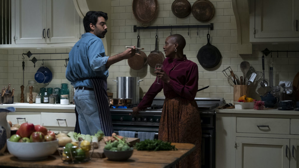 Rahul Kohli as Owen and T'Nia Miller as Hannah. They are standing in a kitchen in front of a large cooker. Owen is holding out a spoon towards Hannah, who is holding a glass of wine. In the foregrounnd is kitchen table covered in vegetables.