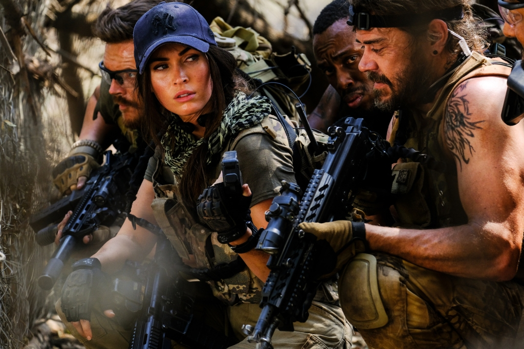 A still from 'Rogue'. Sam O'Hara (Megan Fox) is the image focus, geared up in military combat gear and semi automatic weapons, she is flanked in the South African bush by her comrades, all men, who are looking to her and waiting for a command to shoot or proceed- all people shown are crouched down.