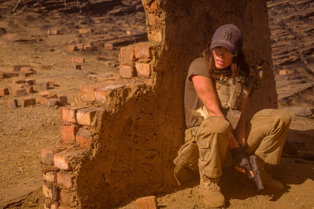A still from 'Rogue'. Sam O'Hara (Megan Fox) is seen here to the right of the image, crouching in fear behind a partially-demolished wall out in a deserted landscape. She is wearing tan combat pants and brown t-shirt with bullet proof vest, dust glasses and Yankees cap. She holds a gun down between her legs, ready to shoot.