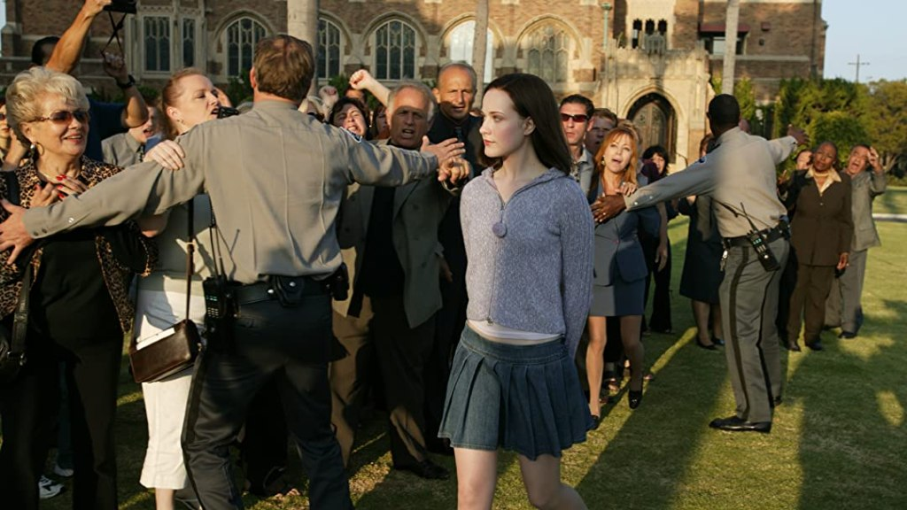 A still from 'Pretty Persuasion'. Kimberly (Evan Rachel Wood) is seen smugly walking across school grounds avoiding a media mob, who are being held back by campus security. Kimberly glances over at a reporter as she walks past the crowd holding her hands behind her back, her hair is dark and she wears a grey zip-up hoodie and pleated denim mini skirt.