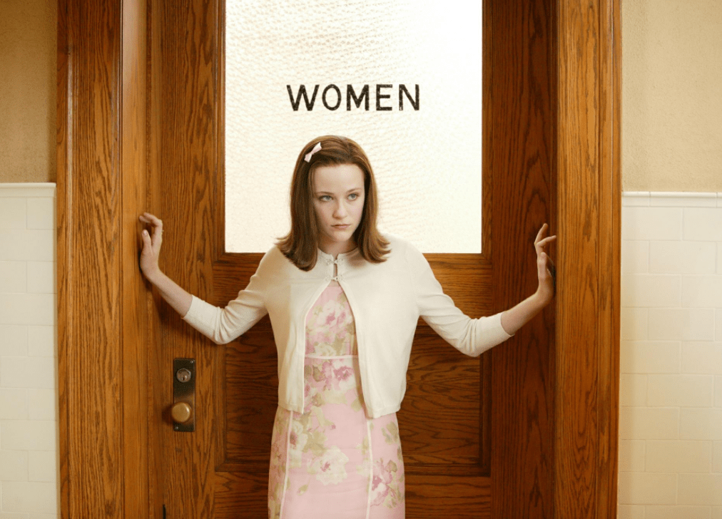 A still from 'Pretty Persuasion'. Kimberly (Evan Rachel Wood) stands centre frame in mid-shot in front of the wooden door for a women's bathroom. Her arms are stretched out across the door frame, as if blocking someone from getting in or out. She is a high-school age girl, white and slim with auburn hair to her shoulders with a pink bow on the left hand side. She wears an entirely pink, overly feminine outfit of a fitted floral dress and slim cardigan with the two top buttons fastened.
