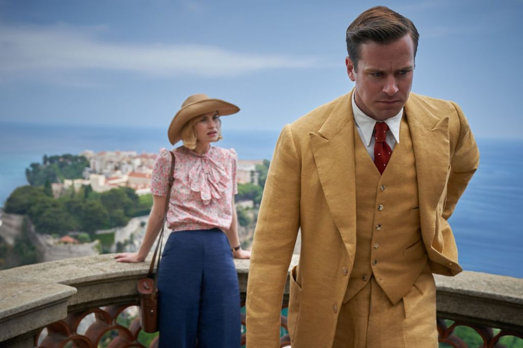 Hammer in a mustard yellow suit walking away from Lily James as she lines back on a stone balcony overlooking the Monte Carlo landscape.