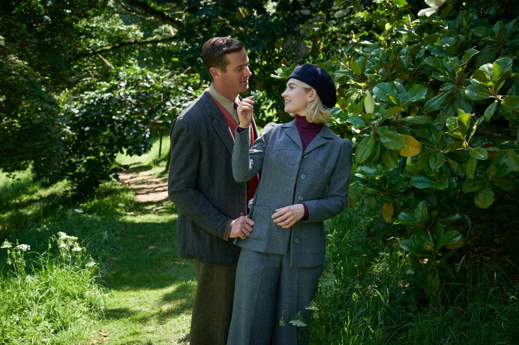 Armie Hammer as Maxim de Winter and Lily James as the second Mrs. de Winter standing in the garden/forest that surrounds Manderly. The gaze upon each other lovingly, on a grassy path under trees.