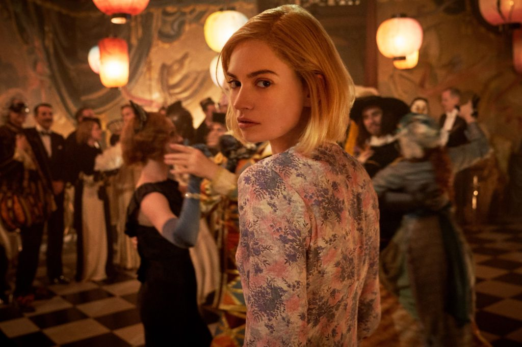 Lily James standing in the middle of a ballroom floor with people dancing around her in costumes. She is dressed in a simple summer dress and looks over her shoulder in distraught.