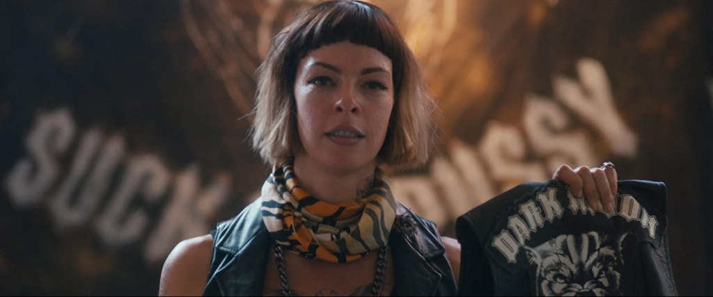 A still from 'Revenge Ride'. Trigga (Pollyanna McIntosh) is shown in close-up, centre frame, holding a leather biker vest with 'Dark Moon' and a wolf's head on it. She has an ombre bob haircut and blunt full fringe. She also wears a leather biker vest and has a tiger print scarf around her neck, with a large silver chain underneath.