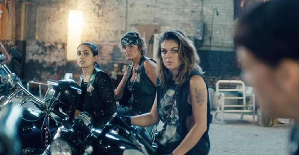 A still from 'Revenge Ride. Three biker chicks are shown sat on their bikes in a garage, looking towards a man who is just almost out of frame to the right hand side of the image. They are all wearing leather vests, tattooed, heavy eyeliner, piercings and bandanas.