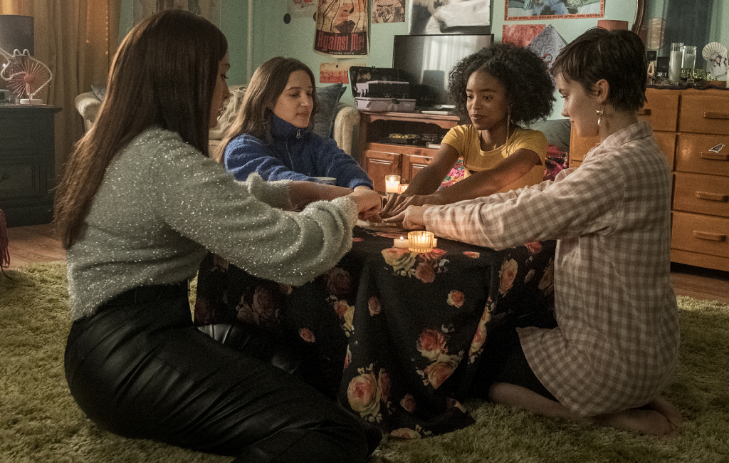 A still from 'The Craft: Legacy'. Lourdes (Zoey Luna), Frankie (Gideon Adlon), Tabby (Lovie Simone) and Lily (Cailee Spaeny) are all sat on a shag rug around a low table covered with a floral tablecloth. Their hands are all in the centre of the table touching a Ouija board.