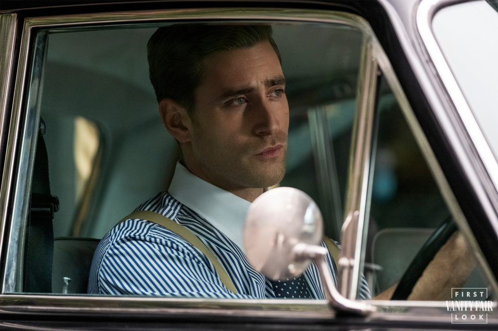 Oliver Jackson-Cohen as Peter Quint in Bly Manor, he is sitting in a car wearing a striped shirt and a spotted tie.
