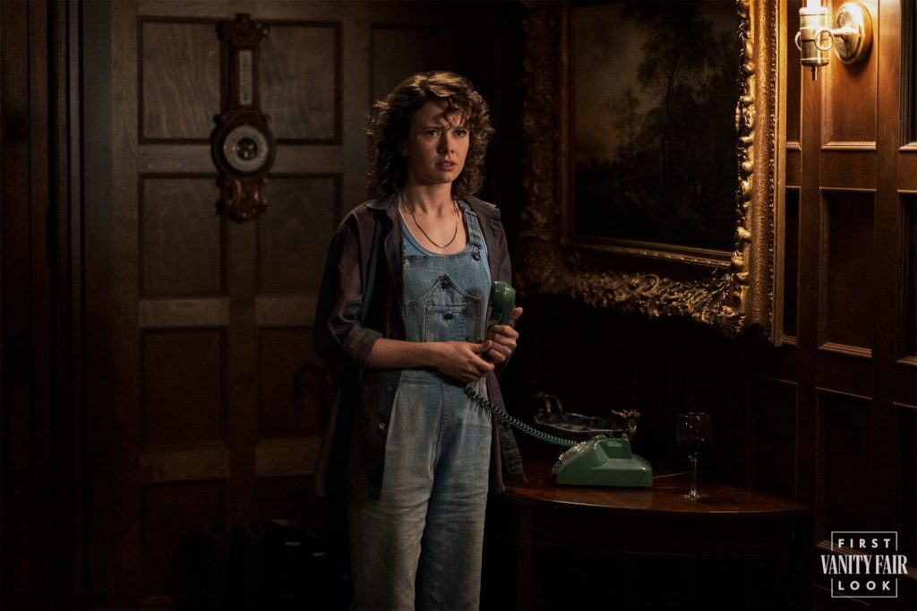 Amelia Eve as Jamie in Bly Manor. She is wearing denim dungarees and a jacket, holding a green telephone. The room is a wood panelled hallway, next to a painting with a gold gilded frame.