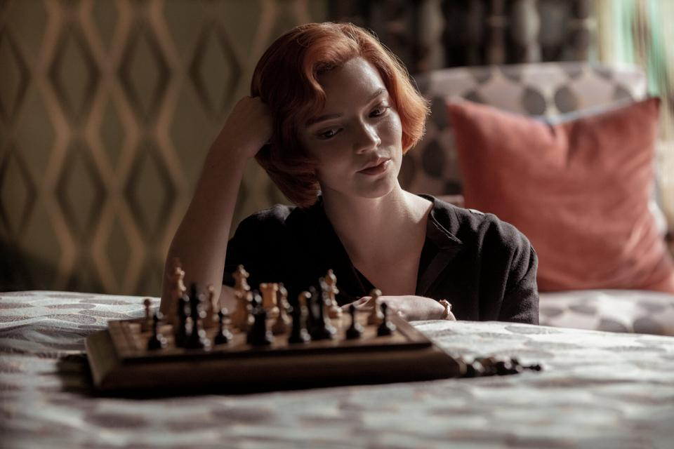 A still from 'The Queen's Gambit'. Beth Harmon (Anya-Taylor-Joy) is sat on the floor, leaning on her bead, one hand supporting her head. She is looking down at a chess board. Beth has a bright red bob hairstyle and is pale skinned with dainty features, She is wearing an open black dress.