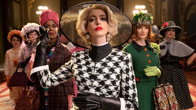 A still from 'The Witches' (2020). The Grand High Witch (Anne Hathaway) is shown in mid-shot, centre frame, flanked by 5 other witches. Each of the ladies wears flamboyant and expensive looking clothing in bright colours in 1950s and 1960s styles. The Grand High Witch wears a Houndstooth jacket with high black collar and elbow length black gloves. She has on a large, wide-brimmed Black sinamay hat and bauble earrings. Her hair is platinum blonde and in a bobbed 1950s style, her lips are red and you can see scars on either side of her lips. She holds  a pair of sunglasses in her left hand.