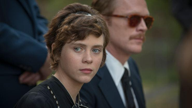 A still from 'Uncle Frank'. Beth (Sophia Lillis) is the focus of the image, with her uncle Frank (Paul Bettany) , out of focus to the right of the image. The pair are at a funeral, dressed in mourning attire. Beth is looking to her left towards someone out of shot.