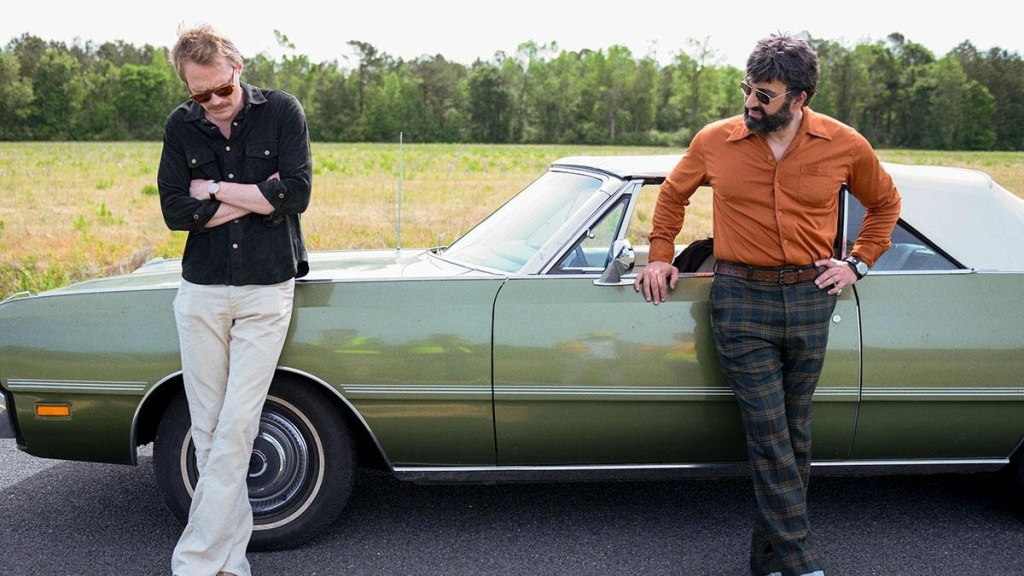 A still from 'Uncle Frank'. Frank (Paul Bettany) stands against his 1970s car on the roadside, next to Wally (Peter Macdissi). Frank is wearing white pants and a black shirt and sunglasses, with his arms folded across his chest as Wally looks on in concern. Wally is wearing an orange shirt and blue/green plaid trsouers and also wearing sunglasses. Wally has dark hair and a full beard and moustache.