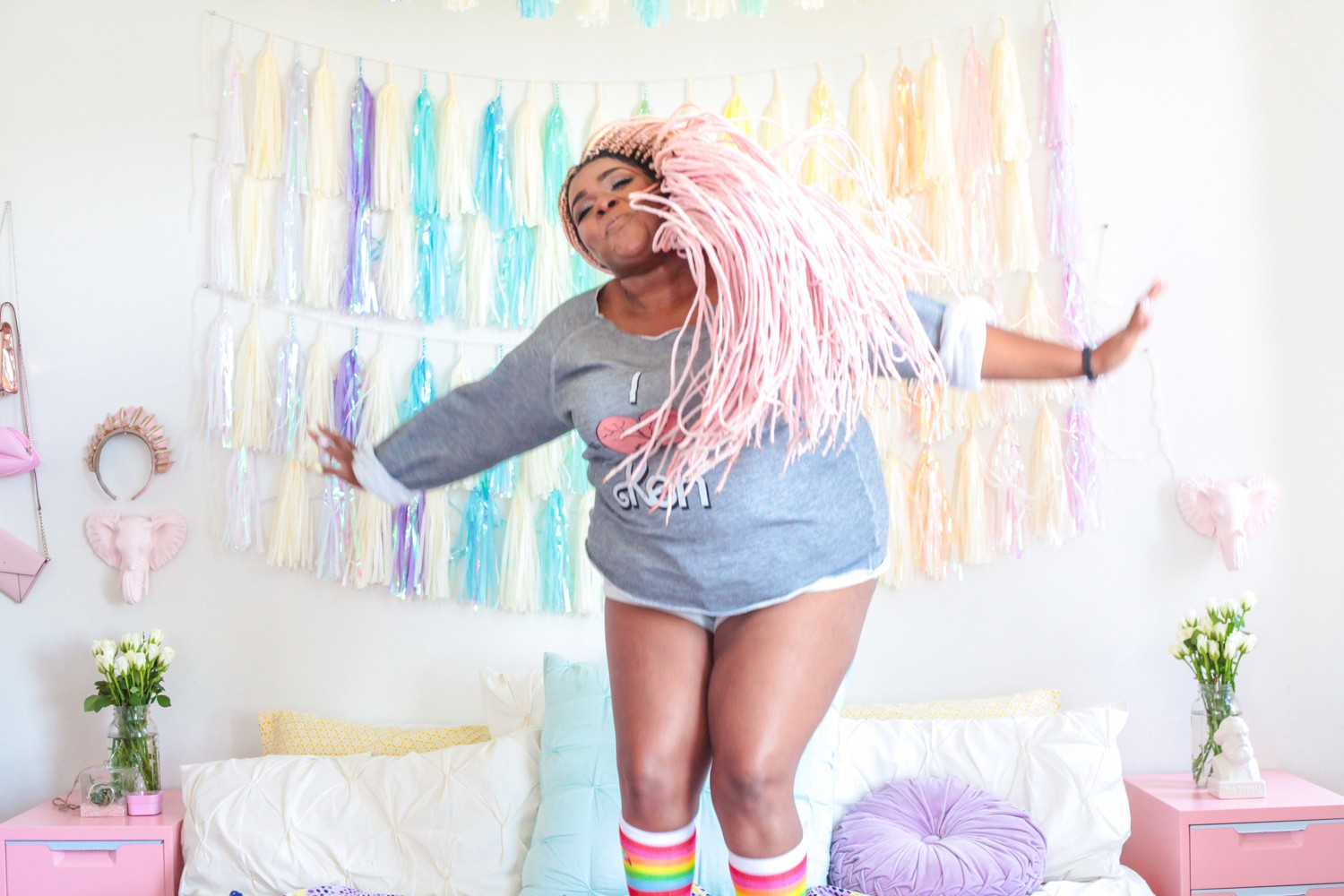YouTuber Amina Mucciolo, jumping on a bed in rainbow socks and flipping her long pink braids.