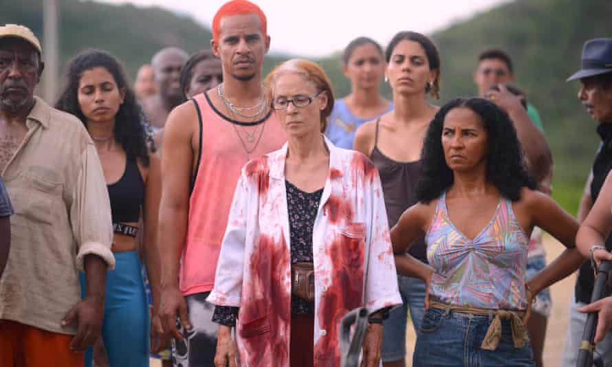 A still from 'Bacurau'. A group of villagers are all standing defiantly wearing a variety of Summer clothes. Domingas (Sônia Braga) is in the centre of the shot and is wearing glasses, a patterned black shirt, and a white lab coat covered in blood stains.