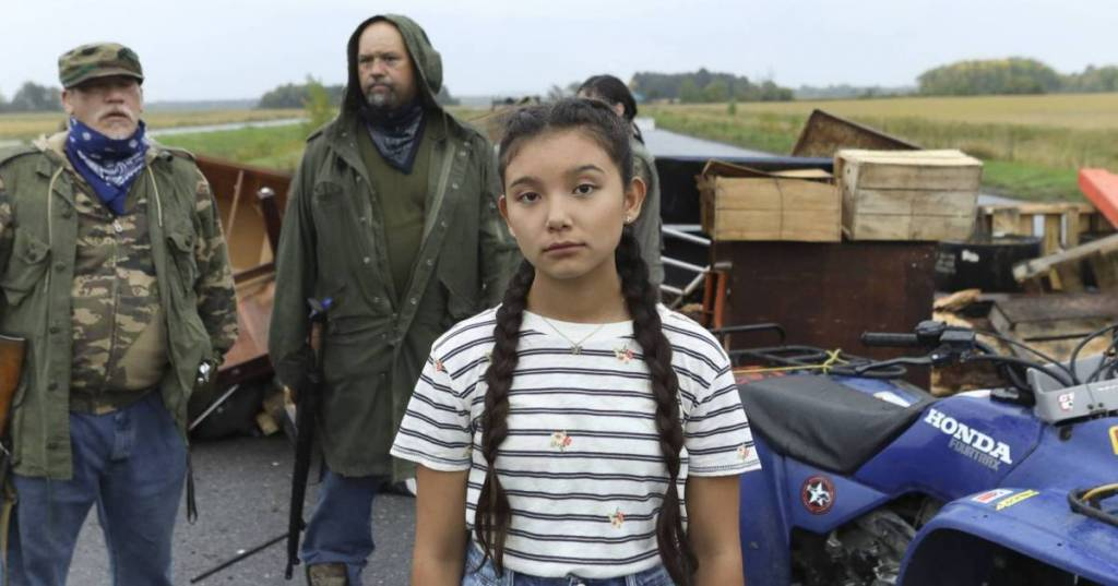 Kiawentiio (who plays Beans) looks directly into the camera, as she stands in the centre of the frame. She is wearing a striped blue and white t-shirt and has her hair in two braids down either side of her face. Behind her are two men in rural-looking outfits and a barricade made of old wood and various items.