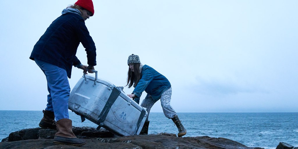 Two young women, in wooly hats and big coats are dragging a big mental crate towards the sea. They are standing on some rocks and in the background the sea stretches out behind them, unfriendly.