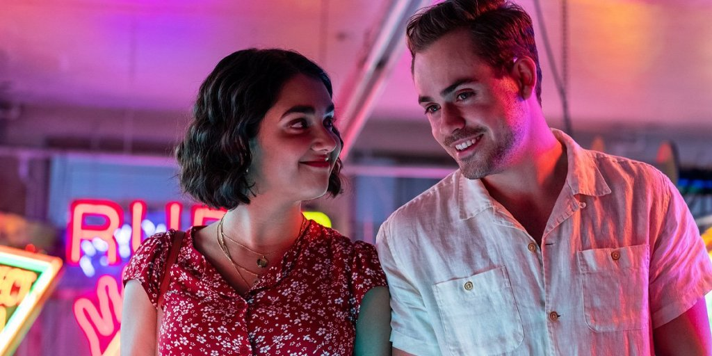 Geraldine Viswanathan and Dacre Montgomery are standing next to each other, lit by neon signs that cast a warm pink glow. Viswanathan is looking at Montgomery with a smile as he looks foward, looking happy.