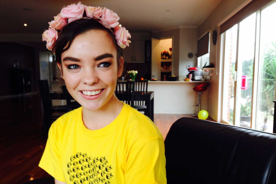 YouTuber Chloé Hayden in one of her videos sitting at a desk, wearing a pink flower crown.