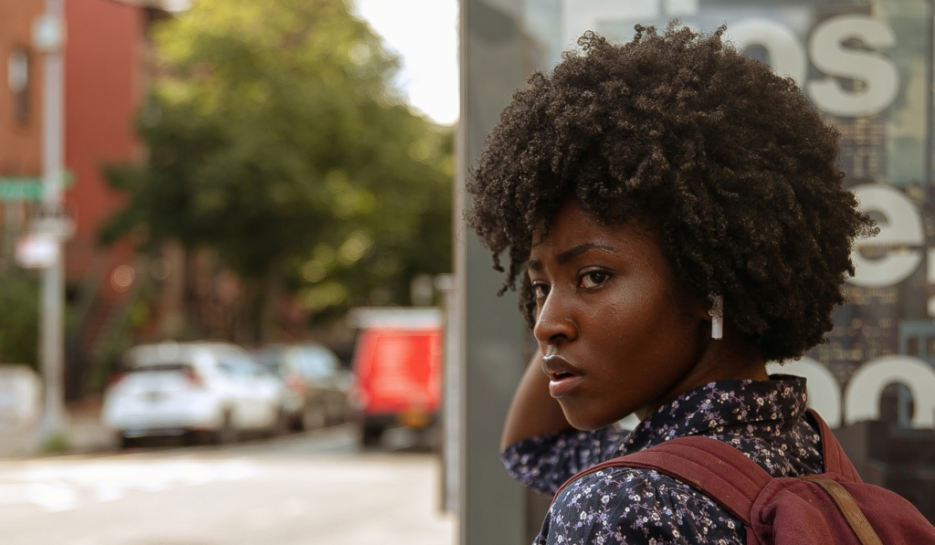 A still from 'Farewell Amor'. Sylvia (Jayme Lawson) is shown in close-up, shot from behind her shoulder as she is walking on a sidewalk. Sylvia is of Tanzanian descent with high cheekbones and a natural, afro hair. She has airpods in and wears a purple/navy floral shirt and red backpack.