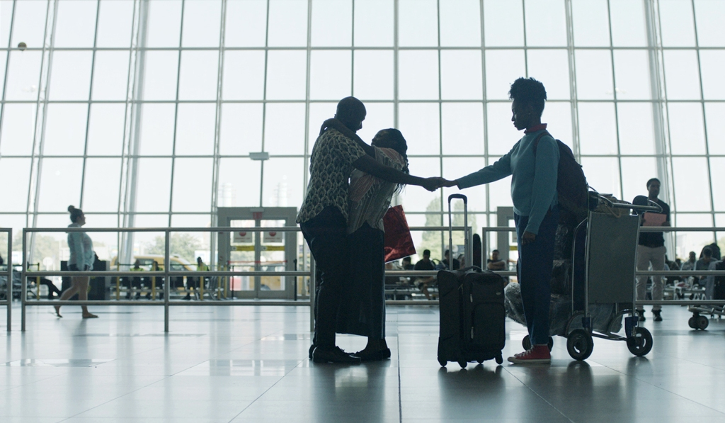 A still from 'Farewell Amor', A Black family is reunited in an airport. They are shot wide, the scope of the glass windows dwarfing their size. A man and woman with brightly printed shirts on hug, as the man reaches behind the woman to hold the hand of a younger woman standing behind her. Luggage is scattered at their feet.
