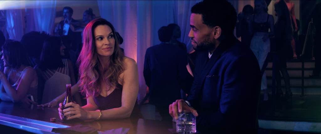 Hilary Swank (Valerie) and Michael Ealy (Derrick) stand next to each other at a bar, purple and blue lighting shining on them from the left. They are both looking at each other in a flirtatious way.