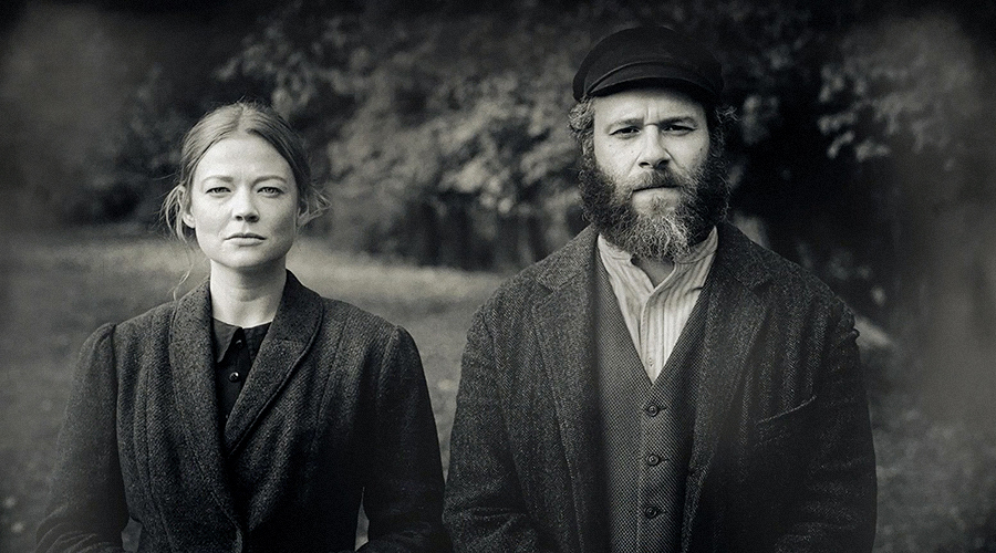 A still from 'An American Pickle'. A black and white photo shows a woman and man (played by Sarah Snook and Seth Rogan) staring seriously at the camera.