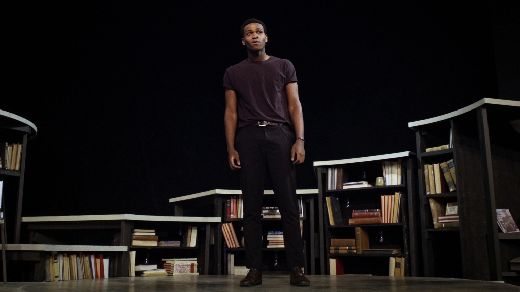 A still from documentary 'Giving Voice'. A young African-American man is onstage, shown in a full-length shot, giving a monologue. He is slim, handsome and dressed plainly in all black. The curtain behind is also black, with steps that resemble book shelves running behind him.