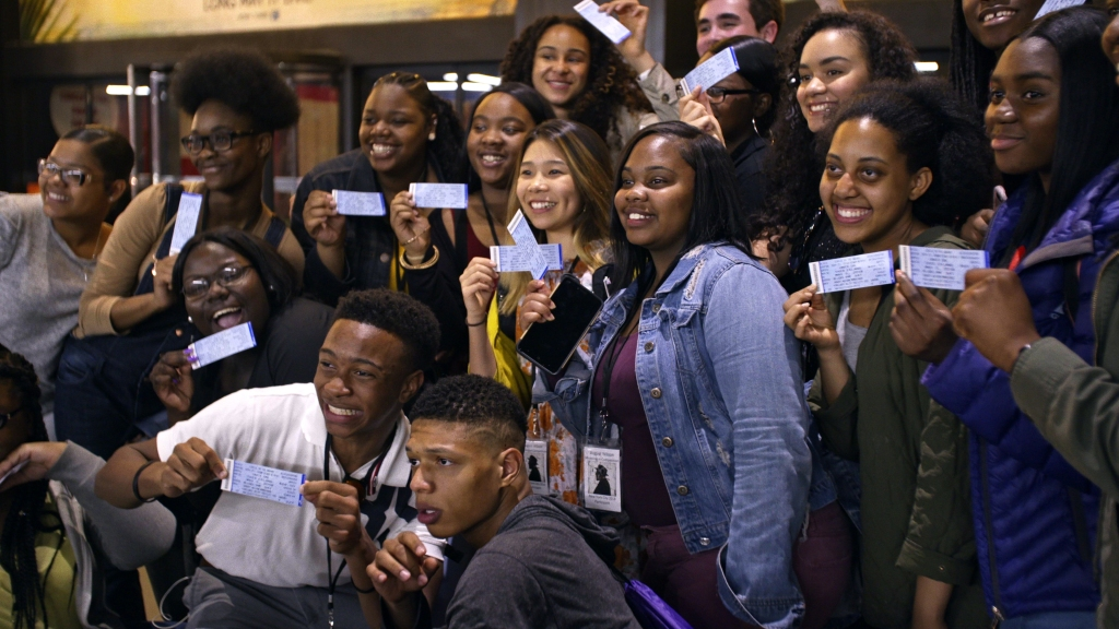 A still from docmentary 'Giving Voice'. a large group of mainly Black students are huddled together for a photograph all holding tickets for the theatre. They are all smiling widely and posing.