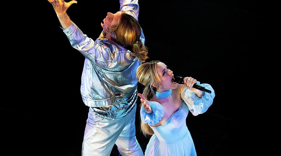 A still from 'Eurovision Song Contest: The Story of Fire Saga'. A man and woman (played by Will Ferrell and Rachel McAdams) are standing back-to-back and singing with their arms raised high.
